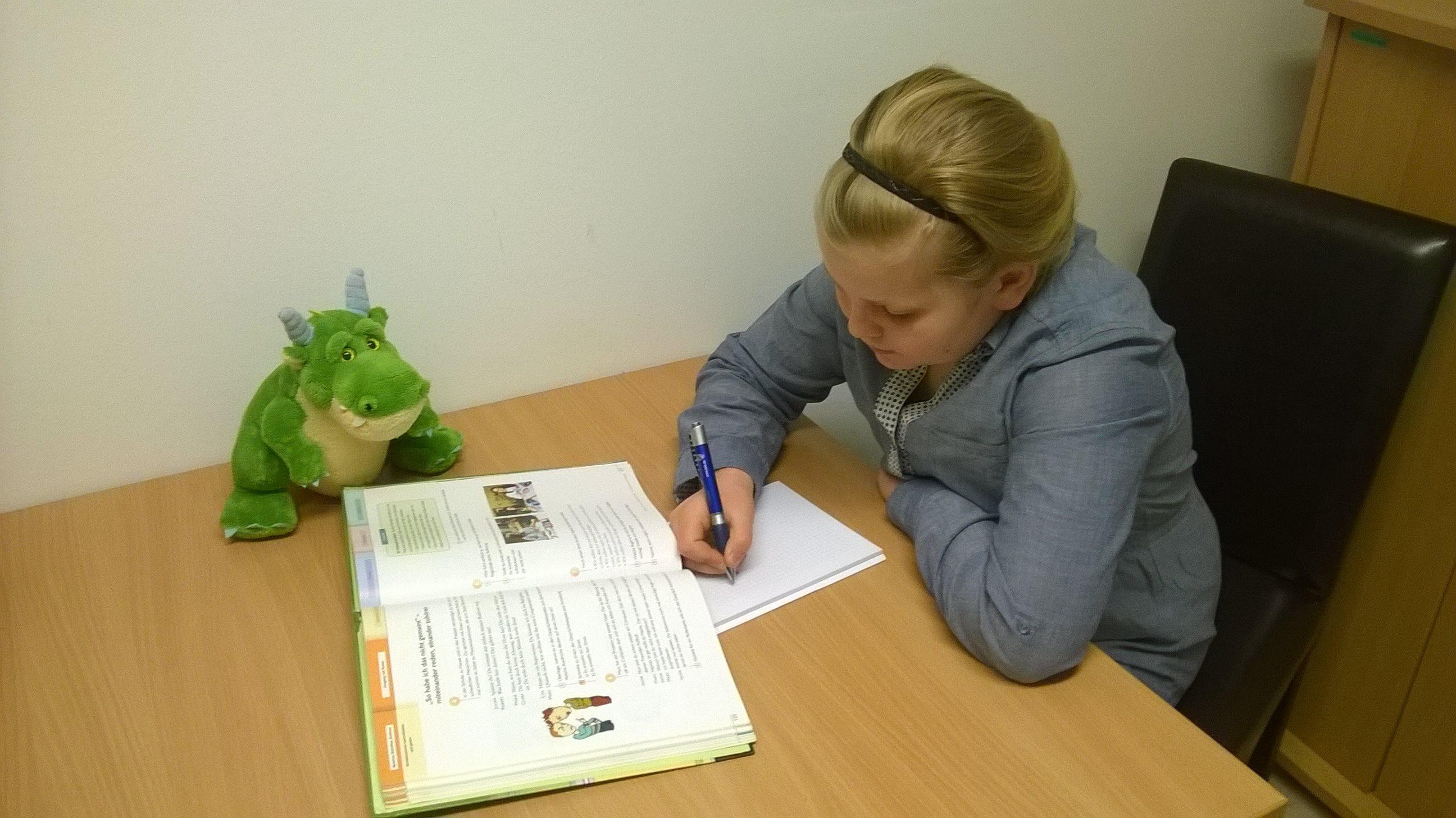 Schülerin vor einem Buch und schreibt in ein Heft